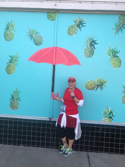Katie poses with a fun umbrella background on the Shark Bite Half Marathon Course.