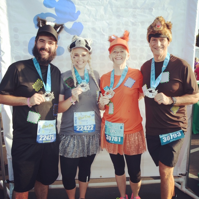 Spencer, Katie, and Katie's parents show off their hard earned medals from the Tinkerbell 10K in Disneyland!