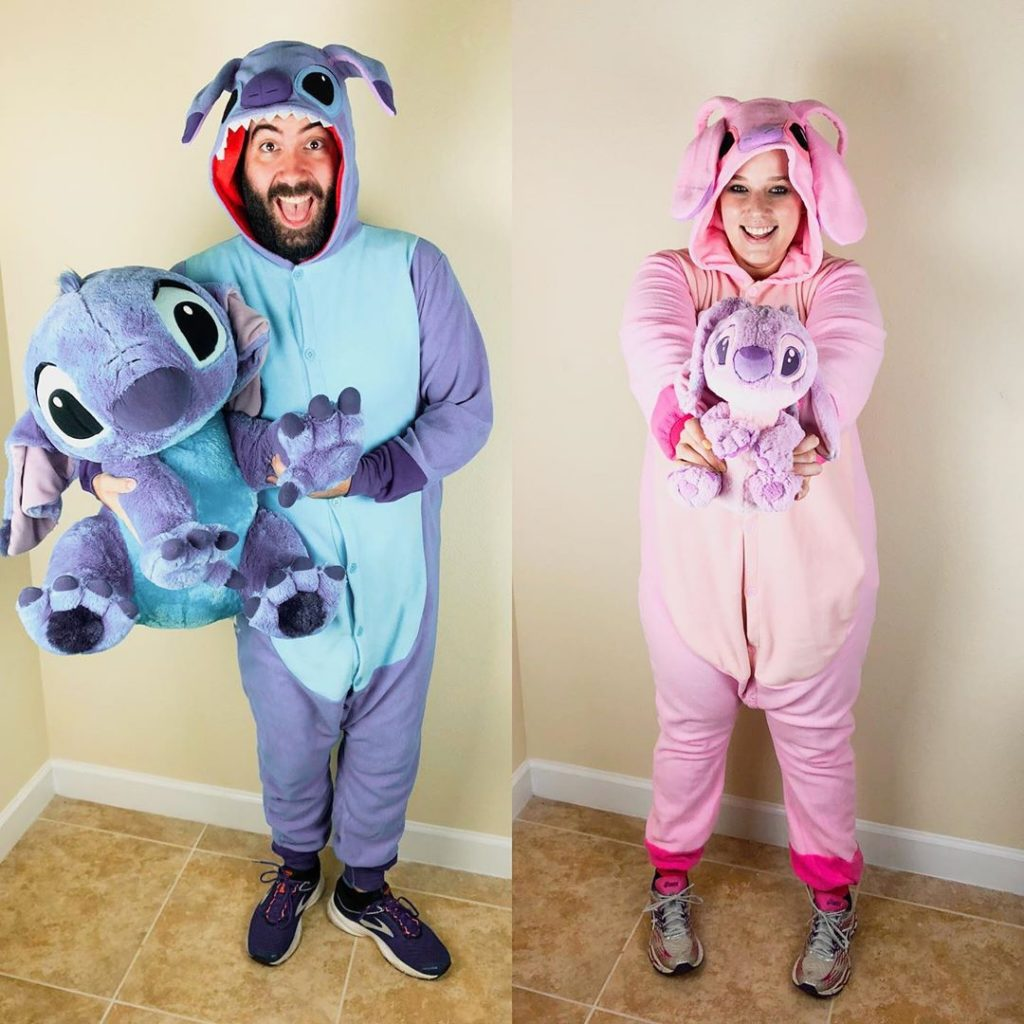Katie and Spencer wearing Stitch and Angel onsies holding plushies