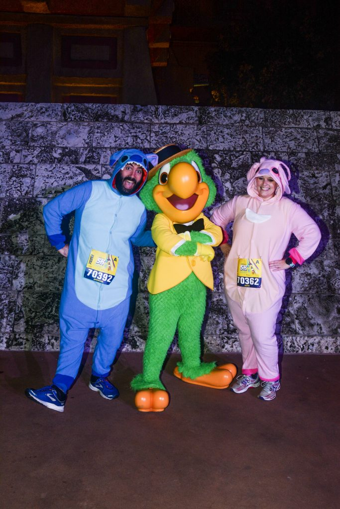 Katie and Spencer in Lilo and Stitch onesies meeting Disney Character Jose Carioca during 2020 Disney World 5K