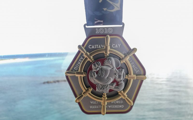 2020 Run Disney Castaway Cay Challenge Medal featuring Captain Minnie Mouse and ships wheel in front of blue water backgroudn