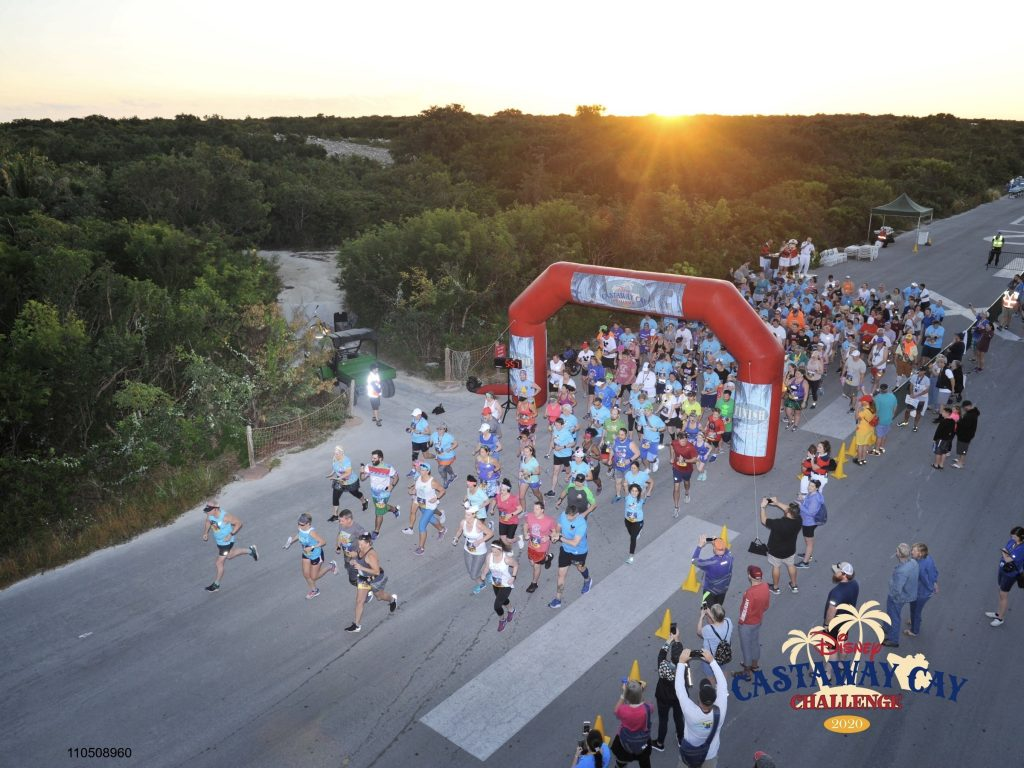 Runners crossing start line of the Castaway Cay Challenge at sunrise