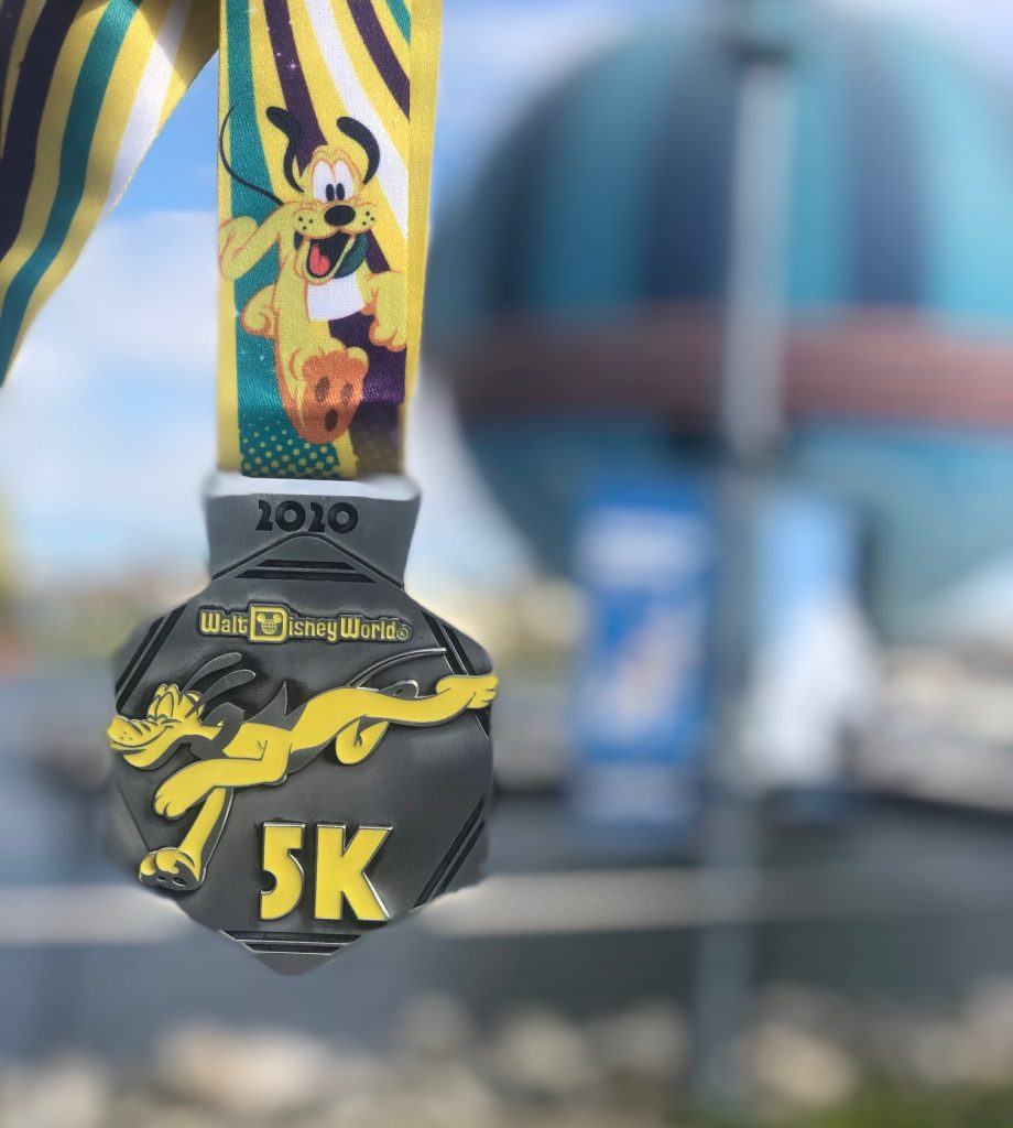 The 2020 Walt Disney World 5K medal featuring Pluto the Dog on a silver hexagon
