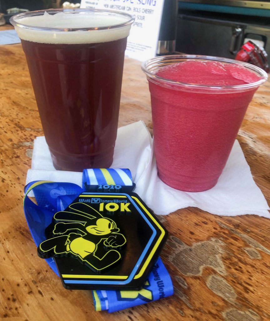 The 2020 Walt Disney World 10K Medal with a beer and frozen drink