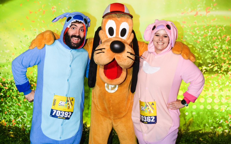 Katie and Spencer dressed in Lilo and Stitch onesies with Pluto the Dog at Walt Disney World 5K