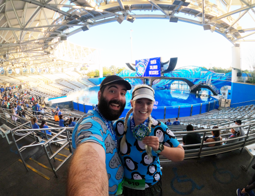 Katie and Spencer holding their Sea World Rescue Run medals in Shamu Stadium