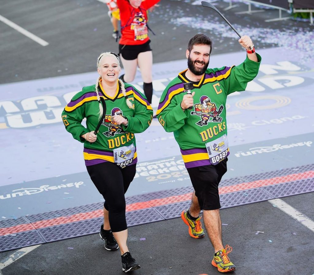 Katie and Spencer crossing the finish line of the 2020 Walt Disney World 10K wearing Mighty Ducks jerseys
