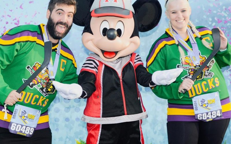 Katie and Spencer wearing Mighty Ducks jerseys carrying hockey sticks with Mickey Mouse wearing sports outfit after 2020 Walt Disney World 10K